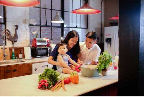 Family enjoy healthy meals with greens in the kitchen